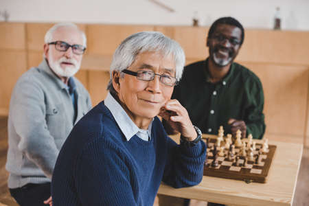 group of happy senior friends playing chess together