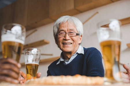 Senior hombre asiático sentado en el bar con amigos y bebiendo cerveza