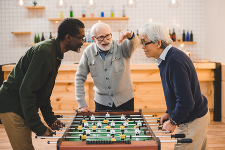 group of handsome senior friends playing table football at bar Stock Photo