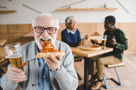 happy senior man eating pizza with beer while his friends talking on background