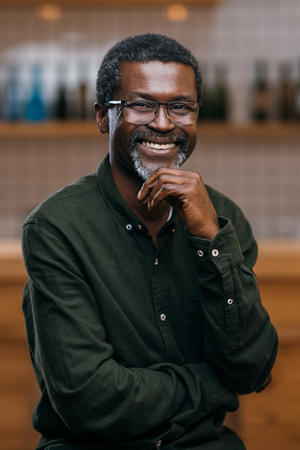 smiling african american mature man in front of blurred bar counter