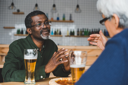 senior friends having discussion at bar while drinking beer with pizza Stock Photo