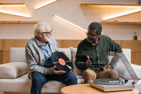 excited senior friends with vinyl record sitting on couch Banque d'images - 104849466