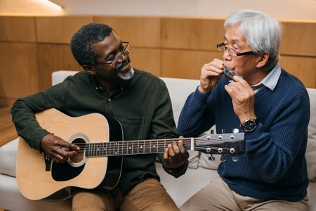 senior friends playing music with acoustic guitar and harmonica