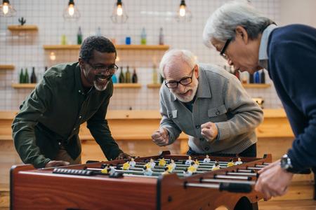 group of senior friends playing table football at bar
