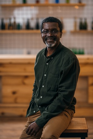 happy african american mature man sitting on chair in bar