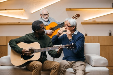 group of senior friends playing music together with guitars and harmonica Reklamní fotografie