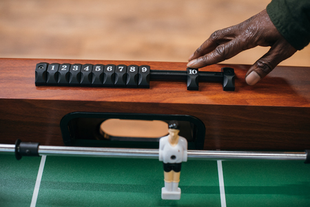 cropped shot of african american man moving counter on table football