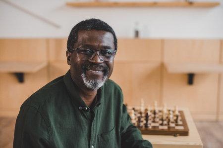 smiling african american man with chess sitting in cafe