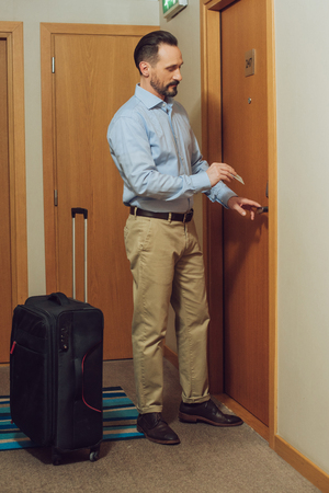 bearded man with suitcase holding card and opening hotel door Stock Photo