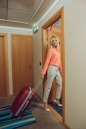 beautiful happy middle aged woman with suitcase entering hotel room