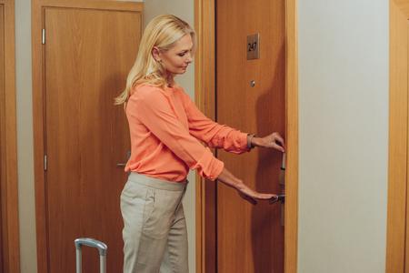 Frau mittleren Alters mit Koffer, der elektronisches Schloss im Hotel öffnet