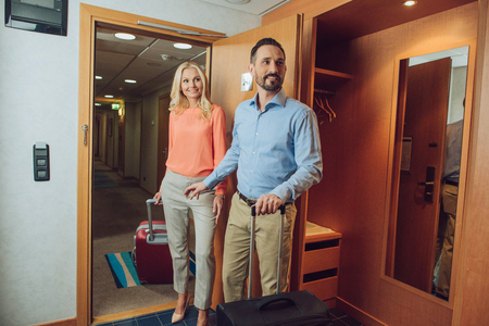 smiling mid adult couple with suitcases looking away while entering in hotel room Stok Fotoğraf