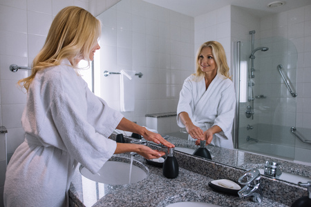 beautiful middle aged woman in bathrobe washing hands in hotel bathroom