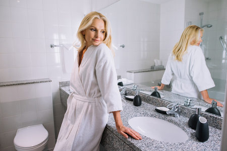 beautiful middle aged woman in bathrobe standing in bathroom at hotel Archivio Fotografico