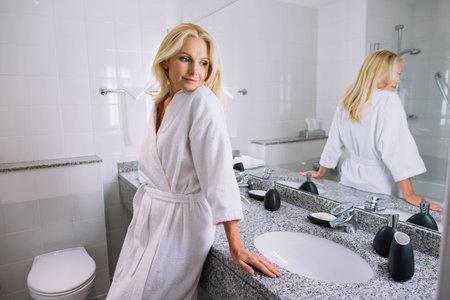 schöne Frau mittleren Alters im Bademantel, der im Badezimmer am Hotel steht