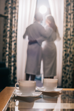 close-up view of cups with hot fresh coffee and couple in bathrobes standing behind in hotel room Standard-Bild - 104533361