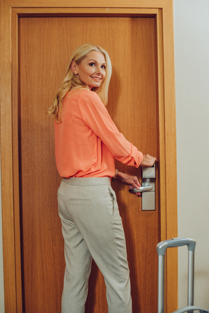 smiling middle aged woman with suitcase opening electronic lock in hotel