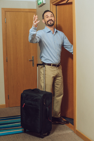 cheerful mature man with suitcase looking away while entering hotel room