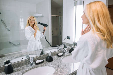 attractive mature woman in bathrobe drying hair with hair dryer in bathroom at hotel Stock fotó