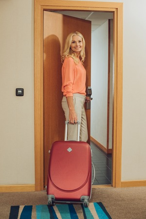 beautiful smiling mature woman with suitcase entering hotel room Stock Photo