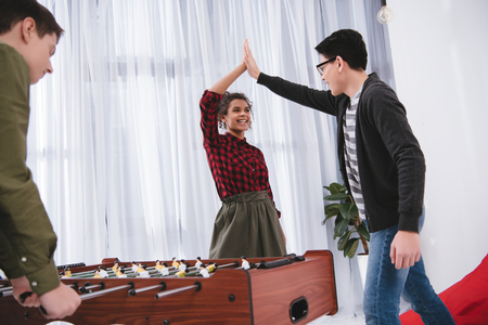 happy cheerful teenagers playing in table soccer