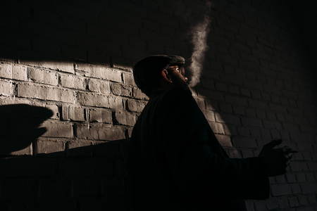silhouette of stylish man smoking in front of brick wall