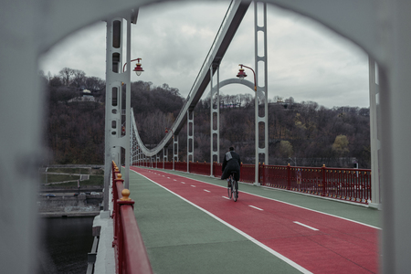stylish man riding bicycle on pedestrian bridge
