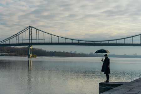 thoughtful man with umbrella standing on river shore 写真素材 - 104533556