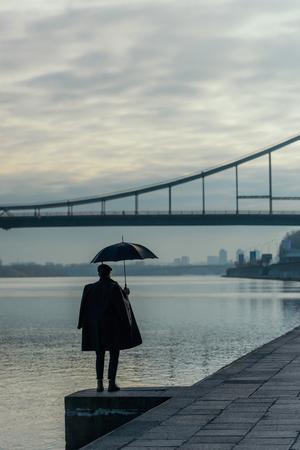 stylish man with umbrella standing on river shore Standard-Bild - 104533561