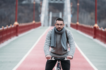 stylish adult man in sweater riding bicycle on pedestrian bridge