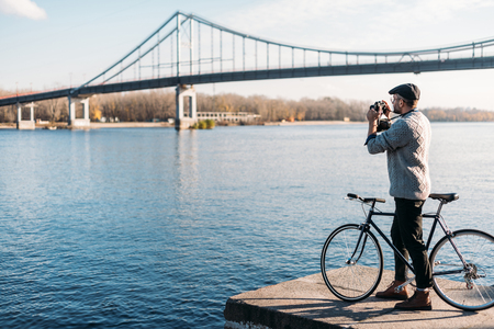 handsome man with vintage film camera and bike standing on river shore 스톡 콘텐츠