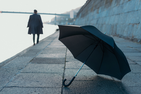 umbrella lying on river shore while man walking blurred on background 写真素材 - 104533631