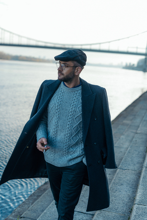 handsome middle aged man walking by river bank with cigarette in hand