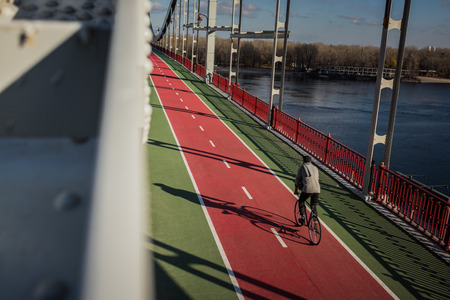 high angle view of man riding bicycle on pedestrian bridge over river