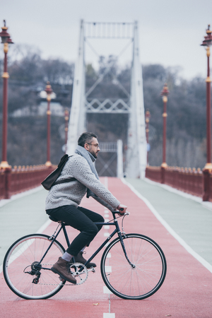 handsome adult man riding bicycle on pedestrian bridge on cloudy day