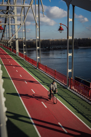 high angle view of adult man riding bicycle on pedestrian bridge over river 写真素材