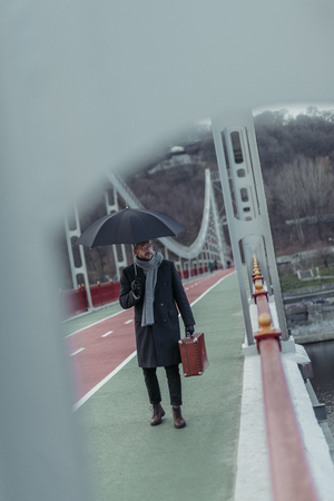 handsome adult man with umbrella and luggage walking by bridge