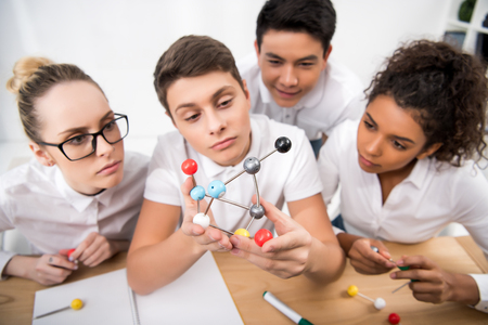 young students picking molecular model for chemistry lesson