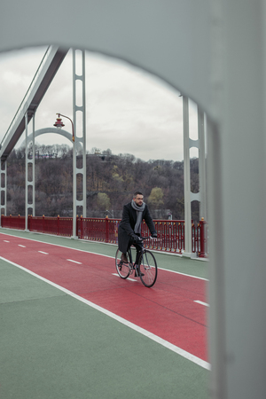 lonely adult man riding bicycle on pedestrian bridge