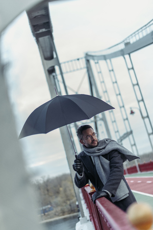 stylish adult man in scarf with umbrella on bridge