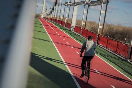 stylish man riding bicycle on pedestrian bridge with biking road 写真素材