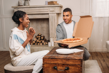 african american man showing pizza to surprised woman at home