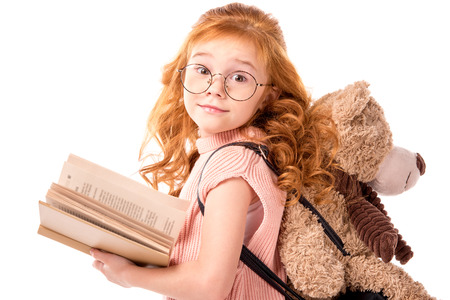 red hair kid standing with book and teddy bear isolated on white