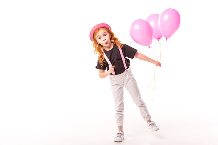 grimacing red hair kid standing with pink balloons on white Stock Photo