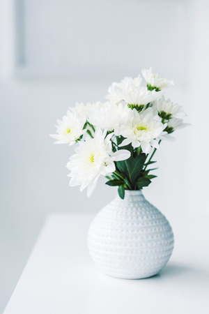 white flowers in modern vase on table Фото со стока