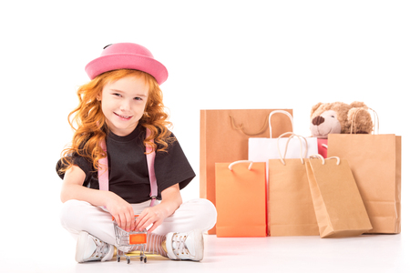smiling child sitting with shopping car toy on white