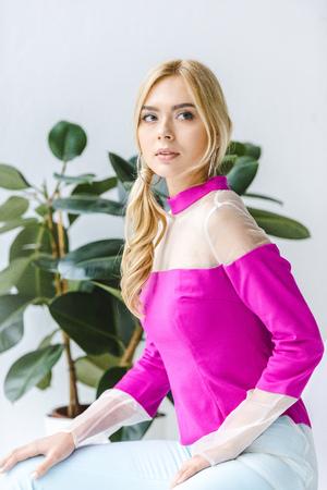 beautiful stylish blonde woman in pink blouse