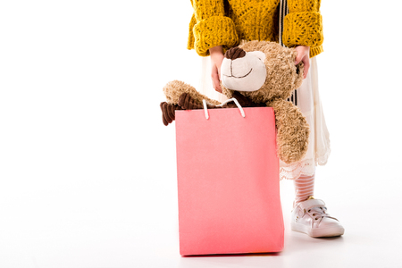 cropped image of kid standing with teddy bear in shopping bag on white Stock Photo