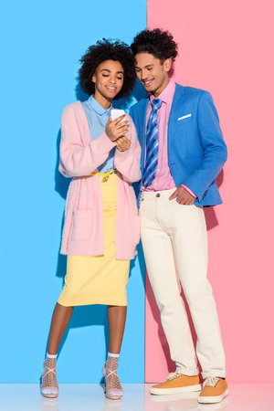 Young african amercian couple looking at phone screen on pink and blue background